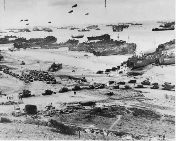 Landing craft, barrage balloons and troops landing in Normandy, France.