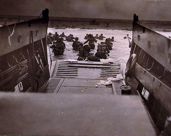 American soldiers wade in from a Coast Guard landing barge.