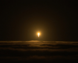 A rocket with the InSight lander punches through the clouds.
